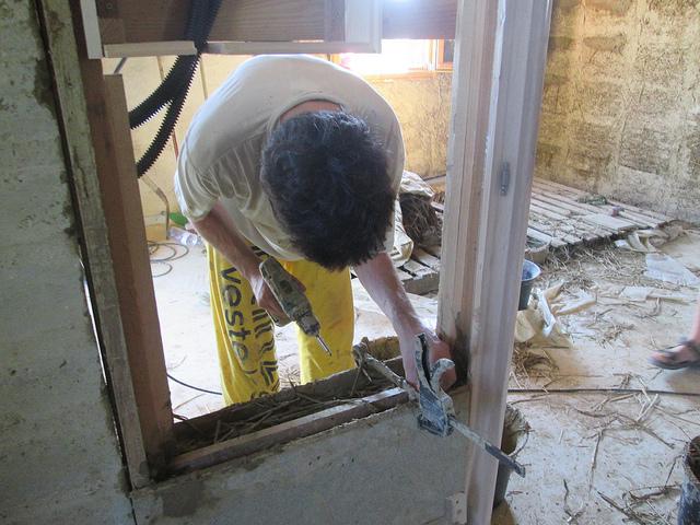 Stephane demarre une brique basse par un coffrage fixé au serre joint pour un bon vissage de départ des deux planches de coffrage (banche) dans lequel il va insérer et tassé le mélange de terre et paille. © gaelle kermen 2015